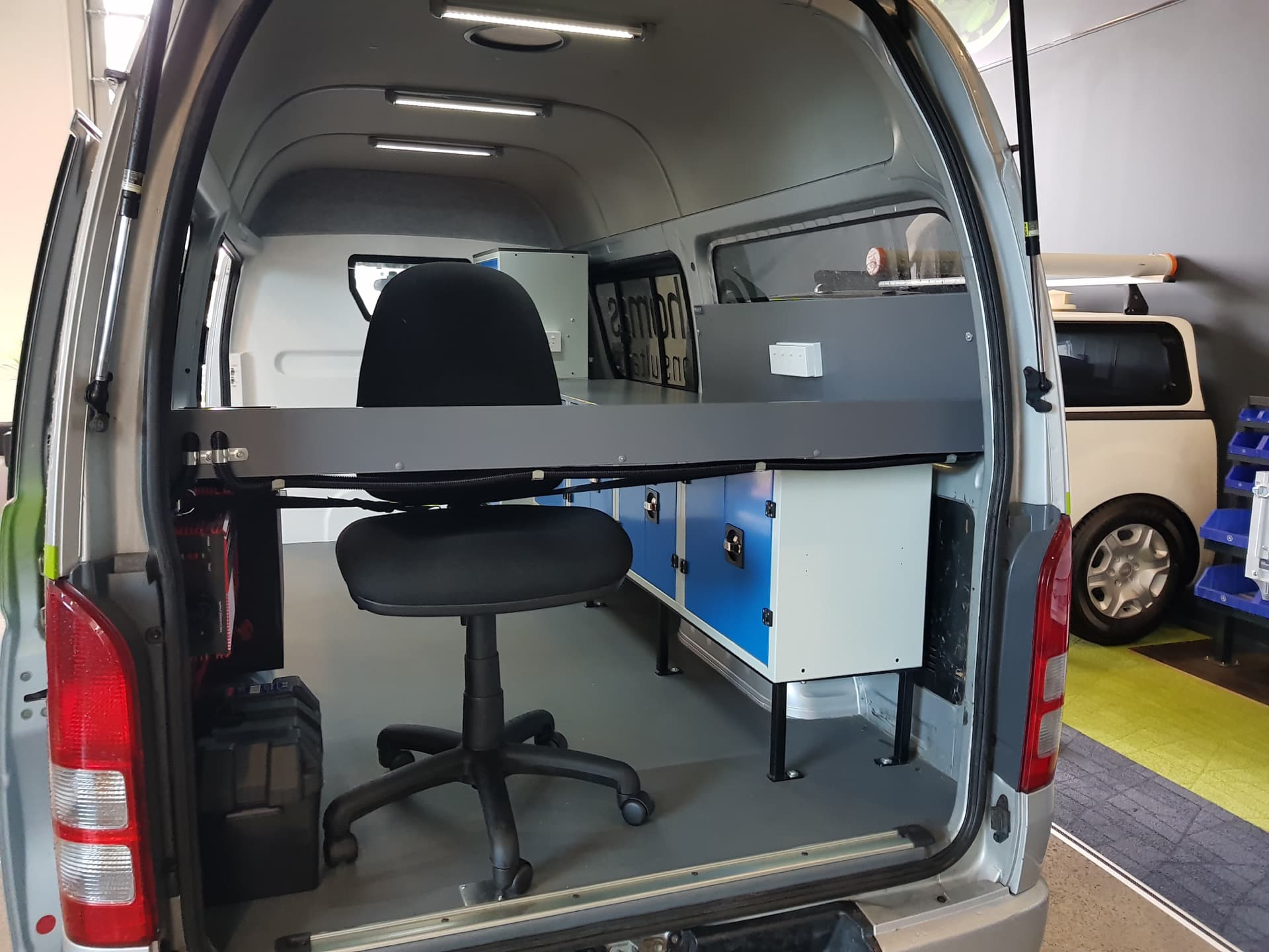 Commercial van fitout with chair and desk setup