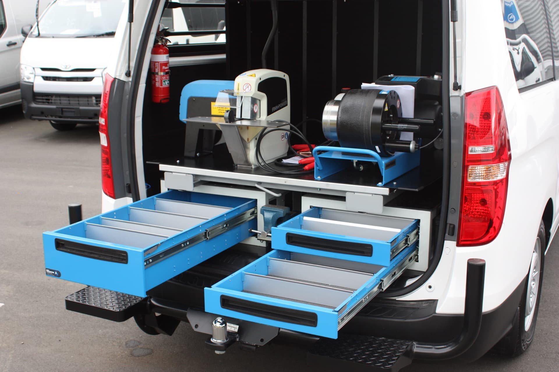 Under floor storage tray drawers and slide out vice in van
