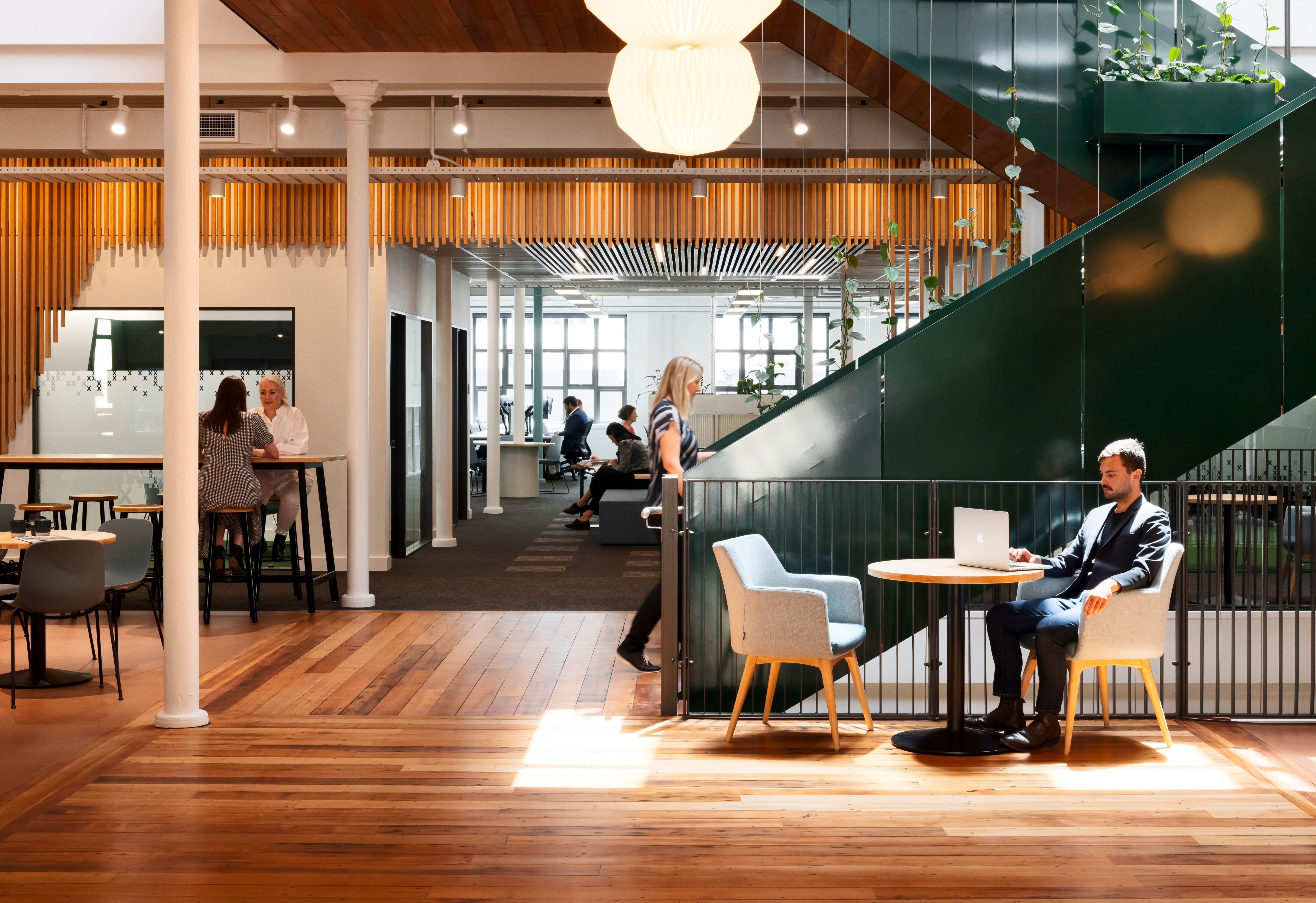 Tables, leaners and soft seating creates differing zones for coworkers to gather and work.