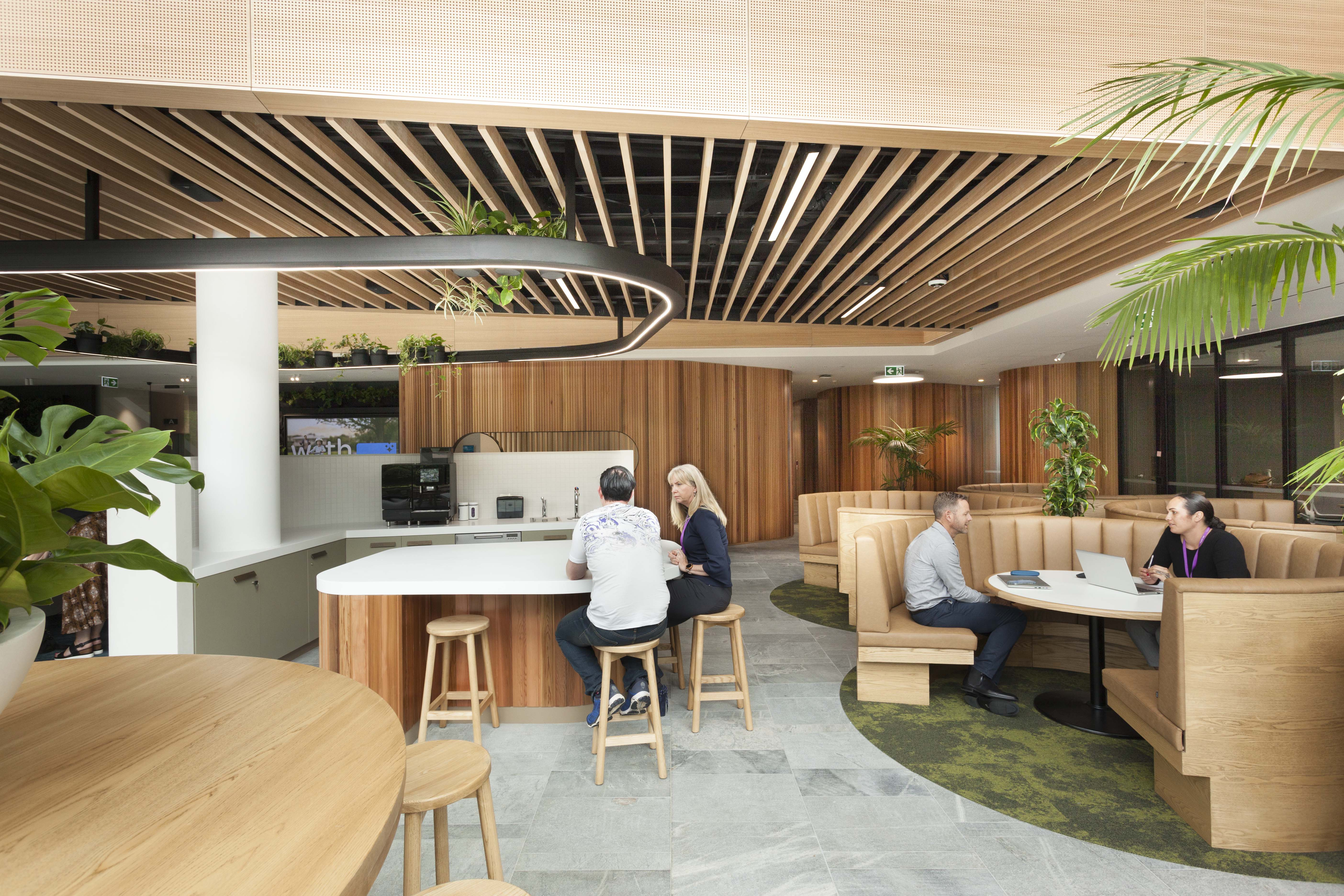 Round banquettes and communal leaners create interactive zones